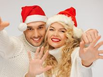 Rodzinna para w pulowerach i Santa kapeluszach Zdjęcia Royalty Free