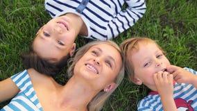 Rodzinna styl życia scena matka i synowie odpoczywa wpólnie na zielonej trawie w parku zdjęcie wideo