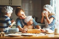 rodzinna szczęśliwa kuchnia matka i dzieci przygotowywa ciasto, półdupki Fotografia Royalty Free