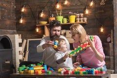 Rodzinna sztuka z szczegółami konstruktor, plastikowe cegły Mamy i dziecka dźwignięcia dłudzy plastikowi bloki trenują Tata trzym obrazy stock