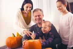 Rodzinnego cyzelowania duża pomarańczowa bania dla Halloween obrazy stock