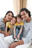 rodzinnego portreta obsiadania uśmiechnięta kanapa zdjęcia royalty free