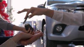 Rodzinnego samochodu zakup, auto handlowiec daje kluczom nowemu samochodowi właściciel ręk rodzice z małym dzieckiem przeciw masz zdjęcie wideo
