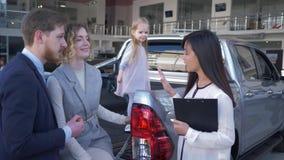 Rodzinnego samochodu zakup, fachowej kobiety kierownik informuje klientom potomstwo pary z dzieciak dziewczyną w bagażniku samoch zdjęcie wideo