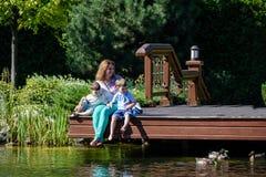 Rodzinnego szczęścia Szczęśliwa matka tenderly obejmuje jego dwa synów dzieci na trawie w wiosna dniu, ciepli uczucia, styl życia Zdjęcia Stock