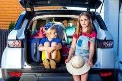 Rodzinnego wakacje walizek labradora psa dziewczyny chłopiec dzieciaka błękita menchii pomarańcze domu słońca lata bagażowego bag fotografia stock