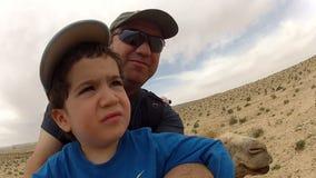 Rodzinni ekstremum sporty: ojciec i syn jedzie wielbłąda zbiory