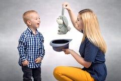 Rodzinny życzliwy, rozrywka Młoda matka pokazuje jej młodemu synowi sztuczka królika w kapeluszu obraz stock