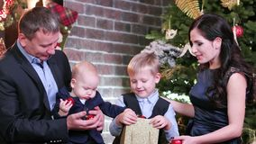 Rodzinny świętuje nowy rok, mama tata i synowie, oglądający Bożenarodzeniowych prezenty siedzieć w żywym pokoju w domu boże narod zbiory wideo