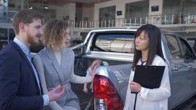 Rodzinny auto kupienie, samochodowego handlowa pracownik pomaga wybierać pojazd dla klientów potomstw dobierać się z dzieckiem w  zbiory