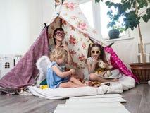 Rodzinny czas: Mama i niektóre siostr dzieci sztuka w dziecko domowej roboty namiocie w domu obrazy stock