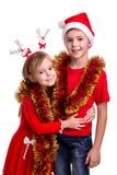 Rodzinny czas, nowego roku świecidełko Szczęśliwy brat z Santa kapeluszem na jego głowie i siostrze z jelenimi rogami, ściska eac zdjęcia stock