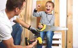 Rodzinny czas: Tata pokazuje jego syn ręki narzędzia, żółtego śrubokręt i hacksaw, Potrzebują musztrować deski dla i musztrować fotografia royalty free