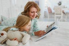 Rodzinny czytelniczy pora snu Ładnych potomstw macierzysty czytanie książka jej córka Matka czyta bajkę jej córka A Zdjęcia Royalty Free