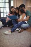 Rodzinny dopatrywanie album fotograficzny wpólnie w żywym pokoju Fotografia Royalty Free
