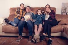 Rodzinny dopatrywanie horror na leżance i łasowanie popkornie w domu obraz royalty free
