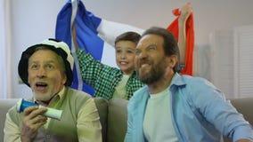 Rodzinny dopatrywanie mecz futbolowy w domu, chłopiec z francuz flagi dopingiem dla zwycięstwa zbiory wideo