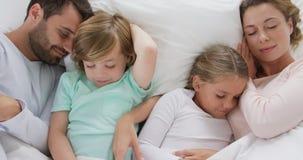 Rodzinny dosypianie wpólnie na łóżku w sypialni przy wygodnym domem 4k zdjęcie wideo
