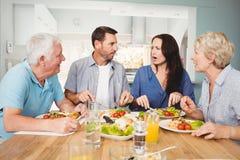 Rodzinny dyskutować podczas gdy siedzący przy łomotać stół Obraz Stock