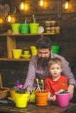 Rodzinny dzień charcica Brodata mężczyzny i chłopiec dziecka miłości natura Kwiat opieki podlewanie Glebowi użyźniacze Szczęśliwy zdjęcia royalty free