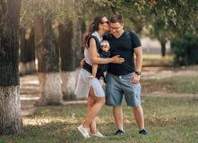 Rodzinny dzień w parku Szczęśliwa potomstwo para z Nowonarodzonym dzieckiem Matka niesie dziecka w ergonomic dziecko przewoźniku fotografia stock