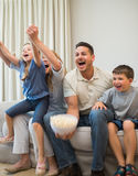 Rodzinny krzyczeć podczas gdy oglądający telewizję Fotografia Stock