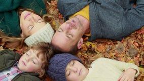 Rodzinny lying on the beach na jesień liściach w parku zbiory