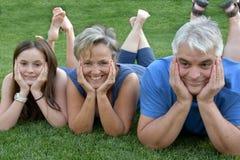 Rodzinny lying on the beach w trawie, ojciec matce i córce, fotografia royalty free