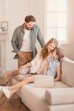 Rodzinny obsiadanie na kanapie i używać w domu laptopie Zdjęcie Royalty Free