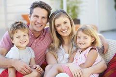 Rodzinny obsiadanie Na Ogrodowym Seat Wpólnie obraz stock