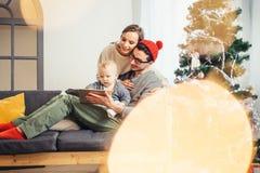 Rodzinny obsiadanie w żywy izbowym mieć zabawę z pastylką ten Święty Mikołaj przynosił obraz stock