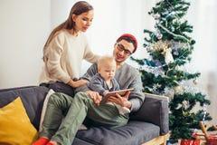 Rodzinny obsiadanie w żywy izbowym mieć zabawę z pastylką ten Święty Mikołaj przynosił obraz royalty free