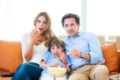 Rodzinny ogląda TV łasowania popkorn zdjęcia stock