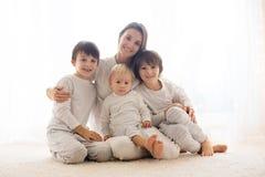 Rodzinny portret matka i jej trzy chłopiec na bielu, fotografia stock