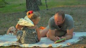 Rodzinny relaksować na koc w lesie i ojciec uczymy troszkę córki czytać zbiory