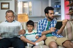 Rodzinny relaksować podczas gdy siedzący na kanapie obraz stock