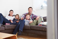 Rodzinny Relaksujący Indoors Ogląda Wpólnie telewizję Zdjęcia Stock