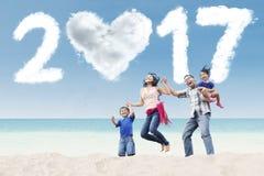 Rodzinny skacze przy plażą z chmurą 2017 Obrazy Stock