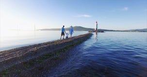 Rodzinny spacer wzdłuż mierzei w kierunku latarni morskiej: rodzice trzymają ich syna ` s ręki zdjęcie wideo