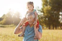 Rodzinny stylu życia pojęcie Szczęśliwy dziad i wnuczka zabawę wpólnie plenerową Popielata z włosami samiec daje piggyback przeja obraz royalty free