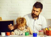 Rodzinny szcz??liwy czas Sztuka z ojcem Tata i syn maluje wp?lnie Czas szko?a Sztuki edukacja obraz stock