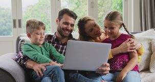 Rodzinny używa laptop na kanapie w wygodnym domu 4k zdjęcie wideo