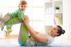 Rodziny matka i dzieciaka syn angażujemy w medytaci i joga ćwiczy w domu, Obrazy Stock