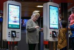 Rodziny rozkazuje jedzenie przy jaźnią - sprawdza out maszynowej i starej damy bawić się telefon komórkowego Fotografia Royalty Free
