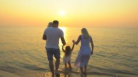 Rodziny słońca plażowy zmierzch Szczęśliwy rodzina składająca się z czterech osób trzyma ręki stoi na marzycielskim piaskowatej p zdjęcie wideo