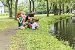 Rodziny z dziećmi blisko do waterscape z kaczką na nim Zdjęcie Stock