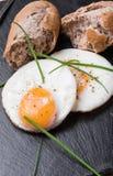 Roeasted γύρω από τα αυγά με το φρέσκο ψωμί στο μαύρο πέτρινο πίνακα Στοκ Εικόνες