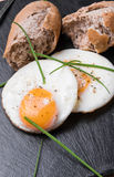 Roeasted Round Eggs with Fresh Bread on Black Stone Board Stock Images