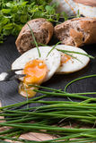 Roeasted Round Eggs with Fresh Bread on Black Stone Board Royalty Free Stock Photography
