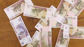 Roebelsbankbiljetten die neer aan houten lijst vallen stock footage